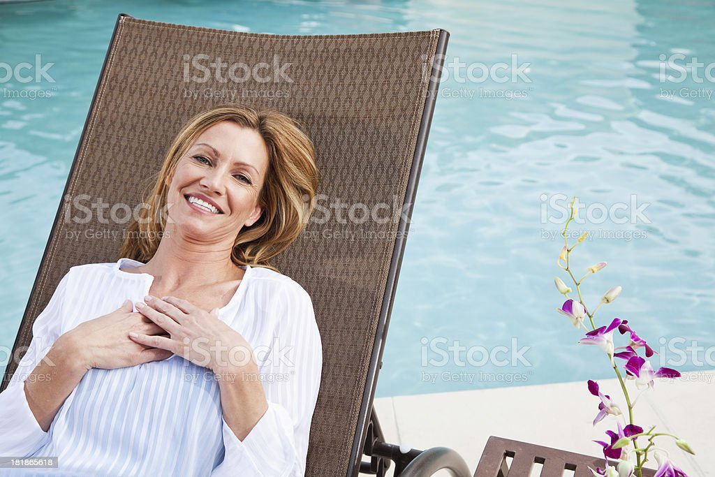 Mature woman relaxing by pool royalty-free stock photo