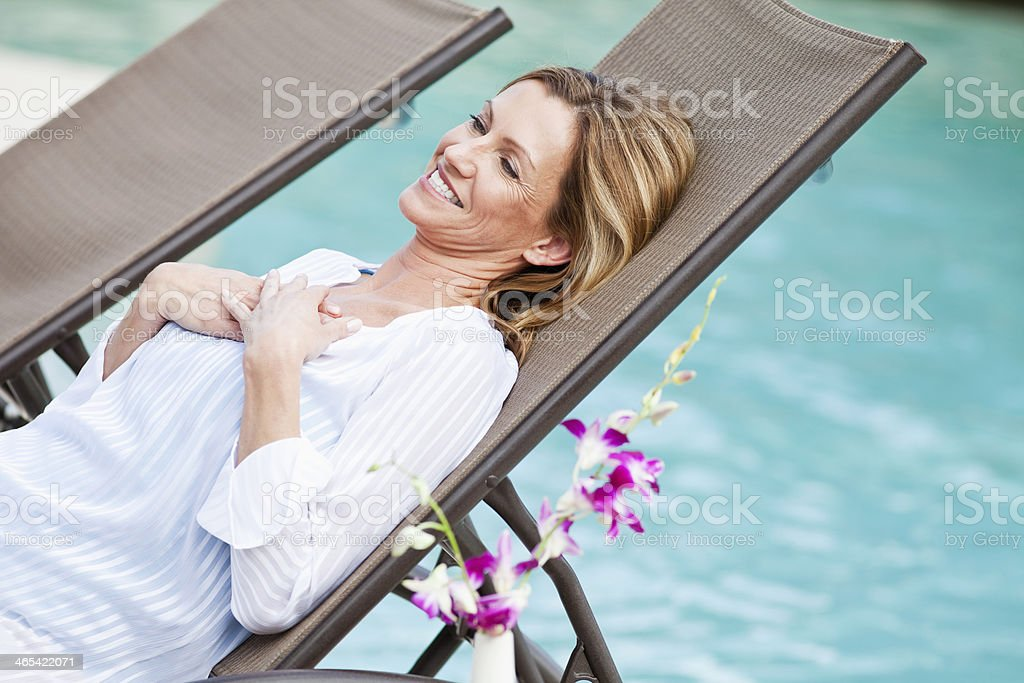 Mature woman relaxing by pool stock photo