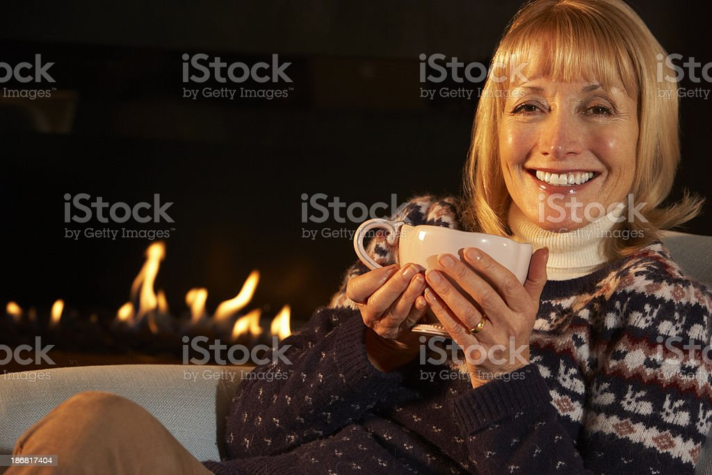Mature woman relaxing in front of fire at home royalty-free stock photo