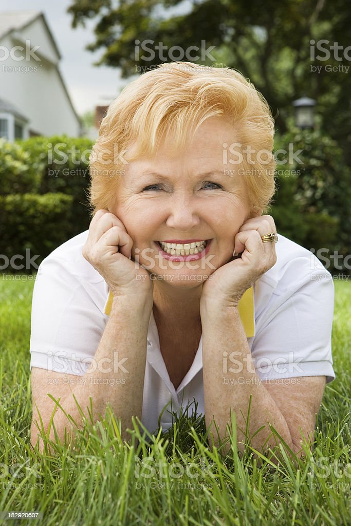 Mature woman relaxing on the grass royalty-free stock photo
