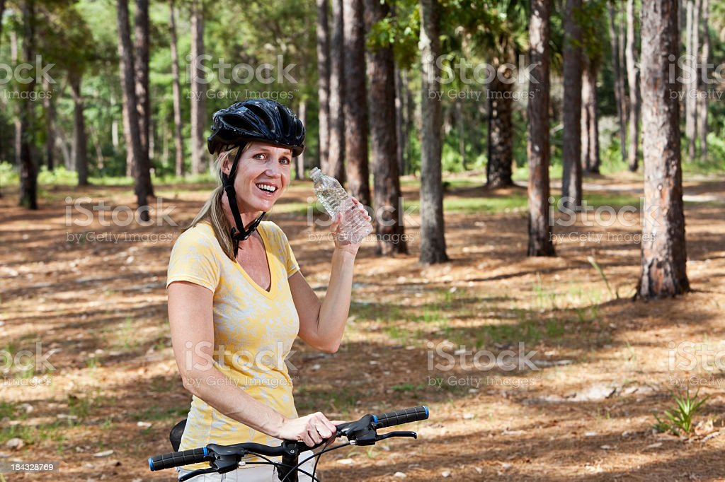 Mature woman riding bicycle in park, drinking water stock photo