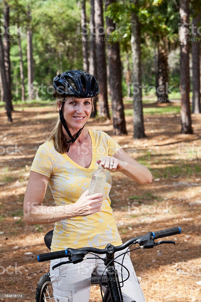 Mature woman riding bicycle in park stock photo
