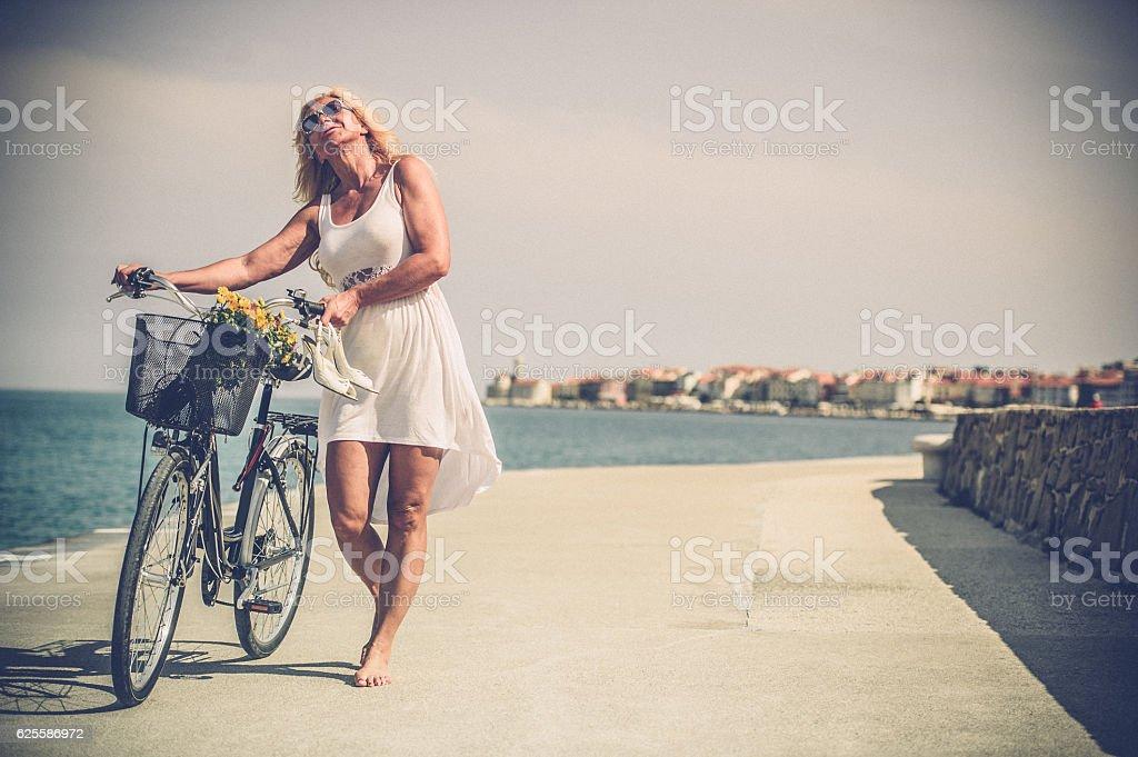 Mature woman riding bicycle stock photo