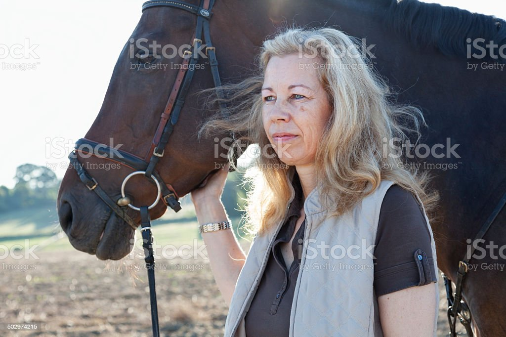 mature woman riding her horse on rural path royalty-free stock photo
