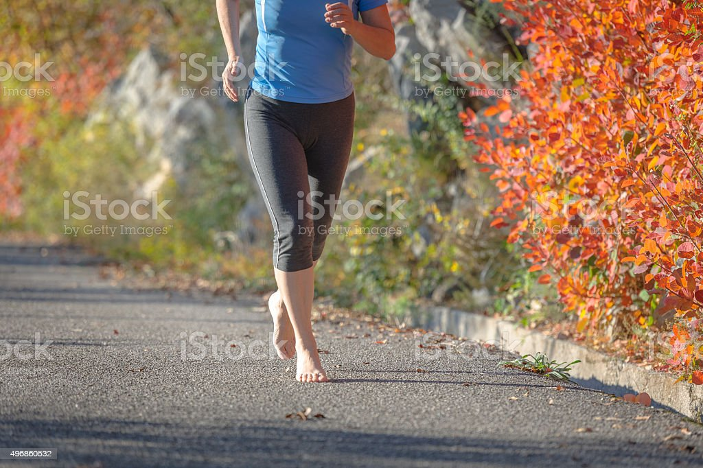 Mature woman running,barefoot runner,leaves, autumn, Slovenia, Europe stock photo