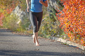 Mature woman running,barefoot runner,leaves, autumn, Slovenia, Europe