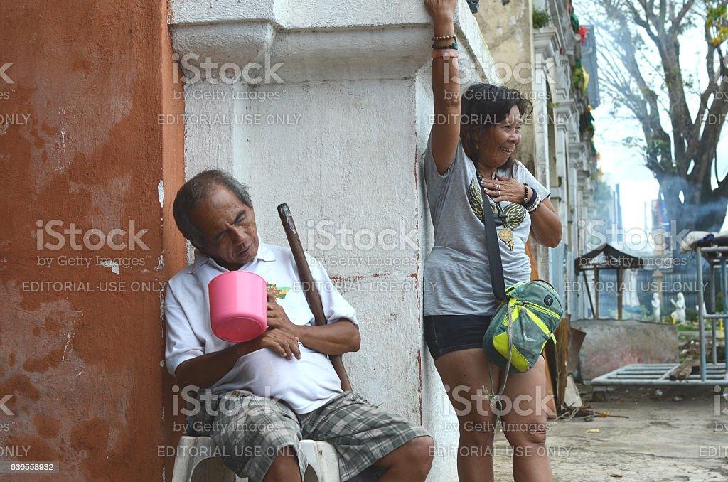 Mature woman Schizophrenic beside blind beggar laughing alone stock photo