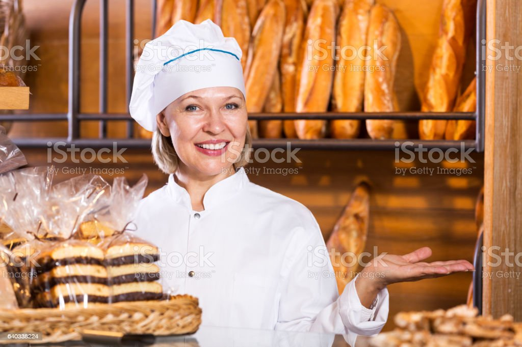 Mature woman selling fresh pastry and baguettes stock photo