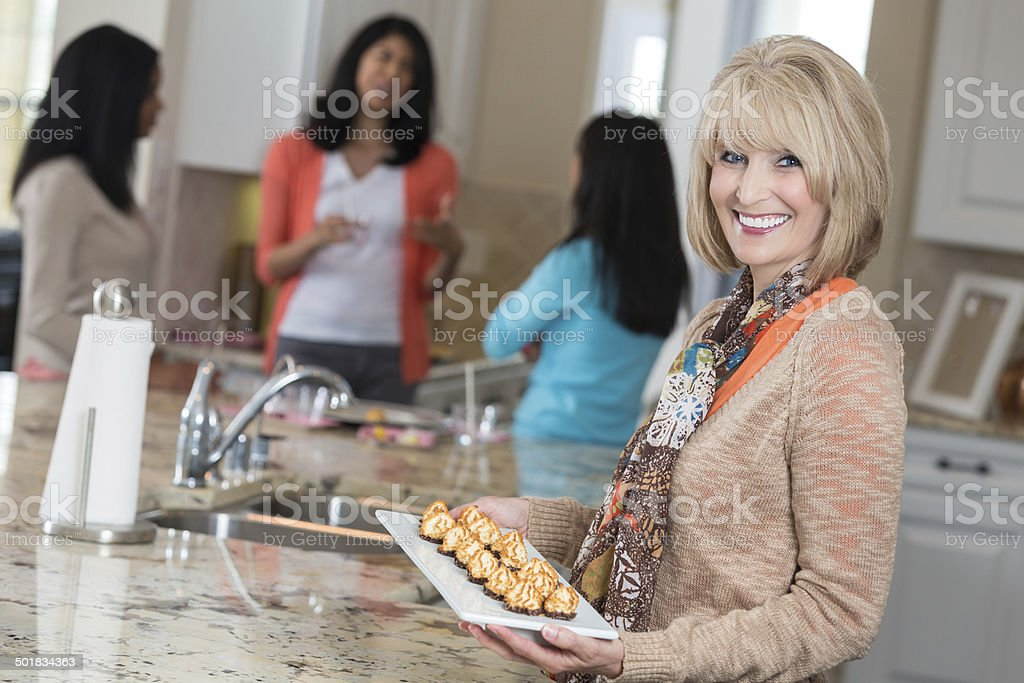 Mature woman serving appetizers to friends at home party stock photo