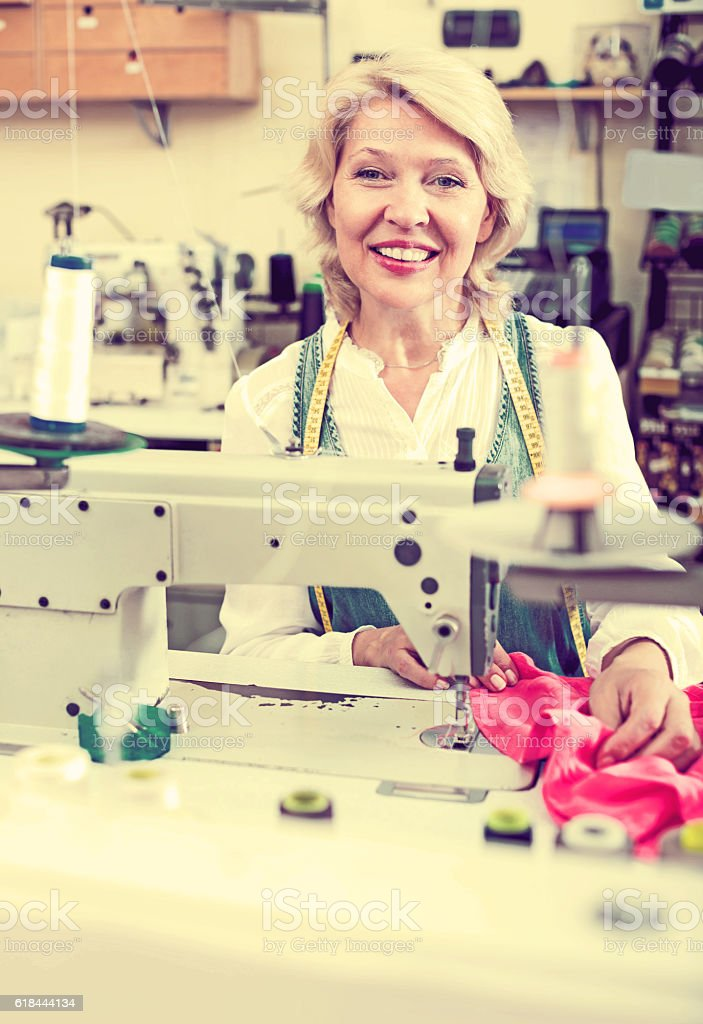 Mature woman sewing with professional machine stock photo