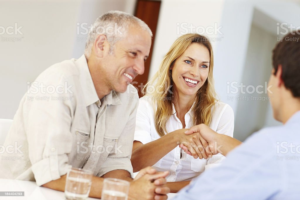 Mature woman shaking hands with young man royalty-free stock photo