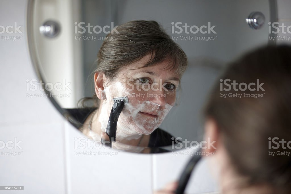 Mature woman shaving face with wet razor stock photo