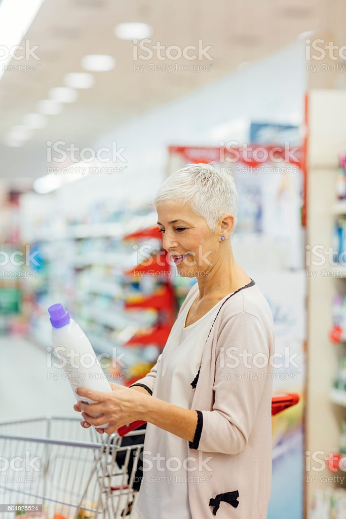 Mature Woman Shopping Home Cleaning Products. stock photo