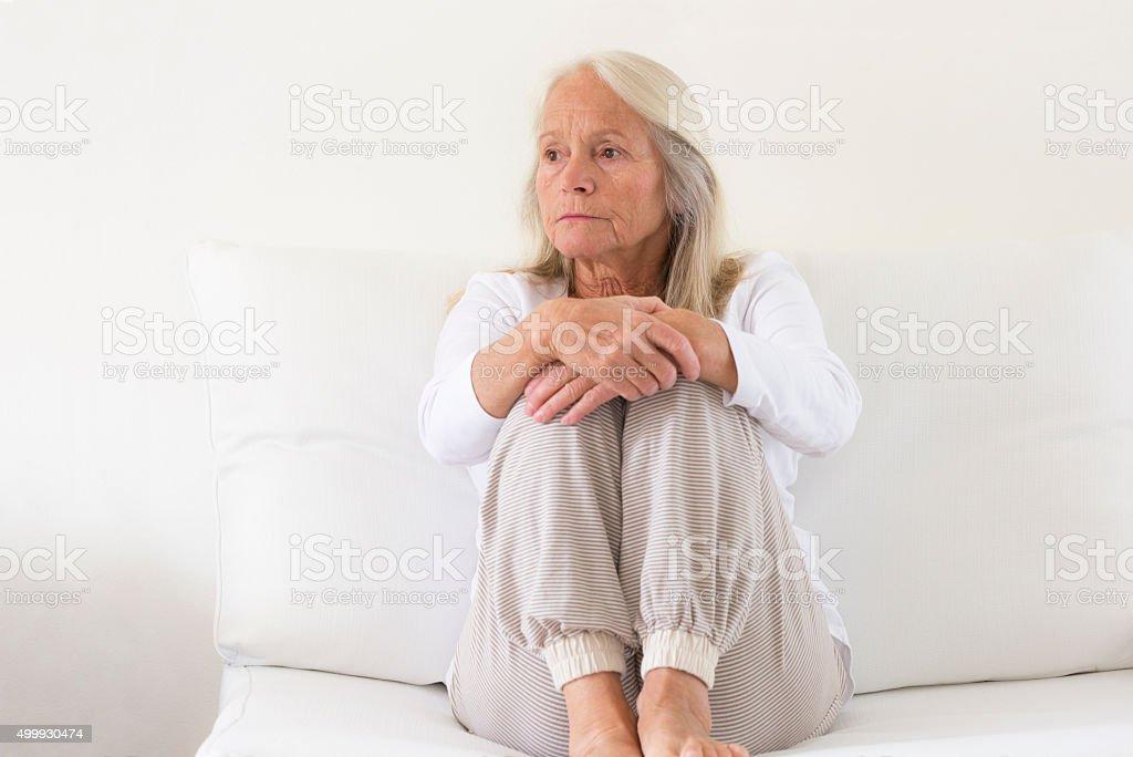 Mature woman sittin on sofa and cuddling knee, copy space stock photo