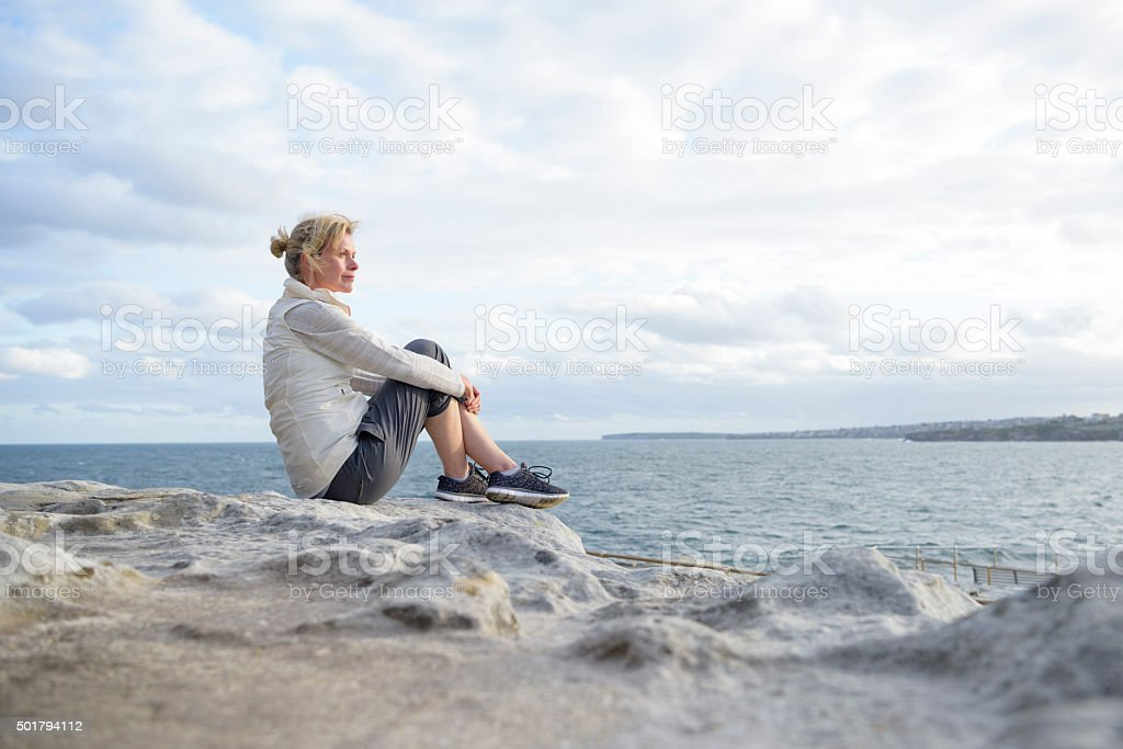 Mature woman sitting alone on rocks, looking at view stock photo