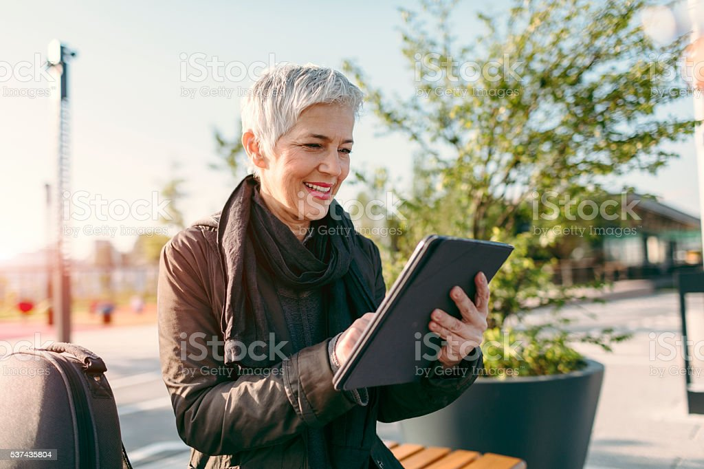 Mature Woman Sitting And Using Digital Tablet. stock photo