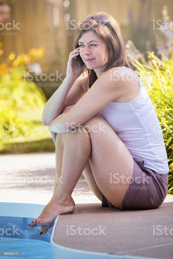 Mature woman sitting at pool with mobile phone stock photo