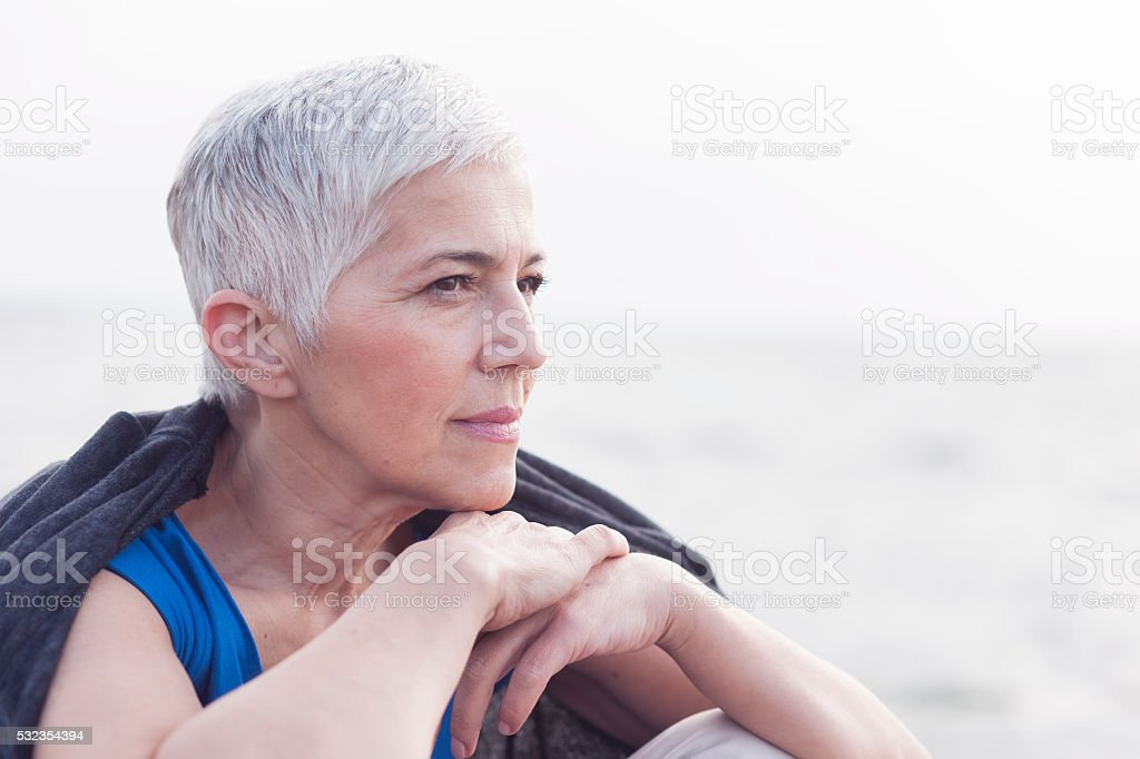 Mature woman sitting near the sea stock photo