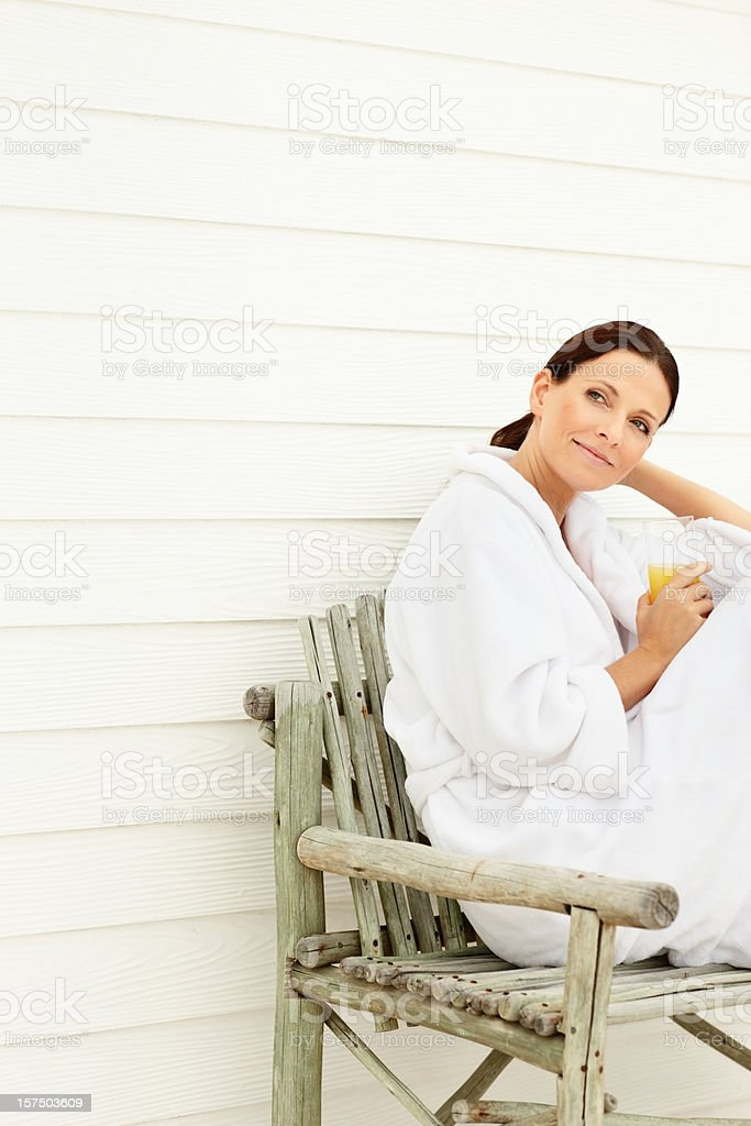 Mature woman sitting on bench with glass of juice royalty-free stock photo