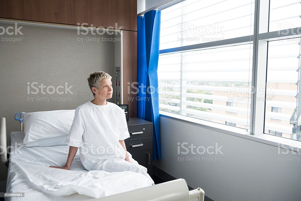 Mature woman sitting up in hospital bed looking through window stock photo