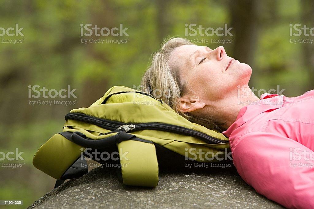 Mature woman sleeping on a rock royalty-free stock photo