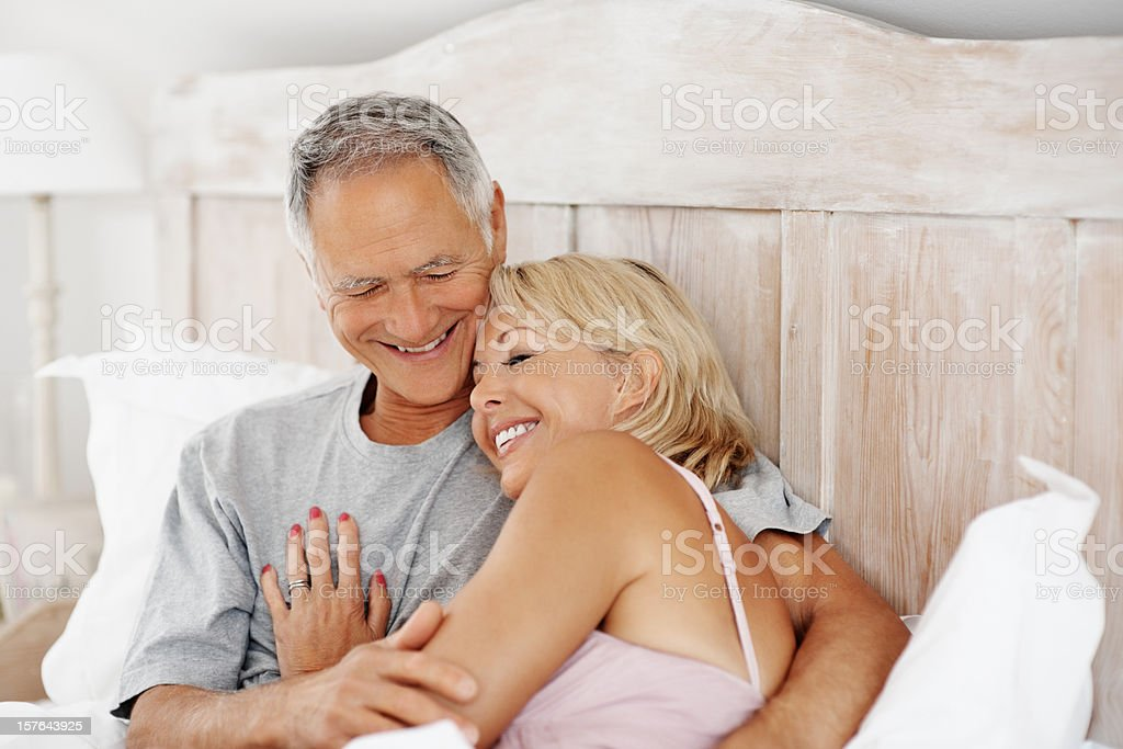 Mature woman sleeping on husband's chest  in bed royalty-free stock photo
