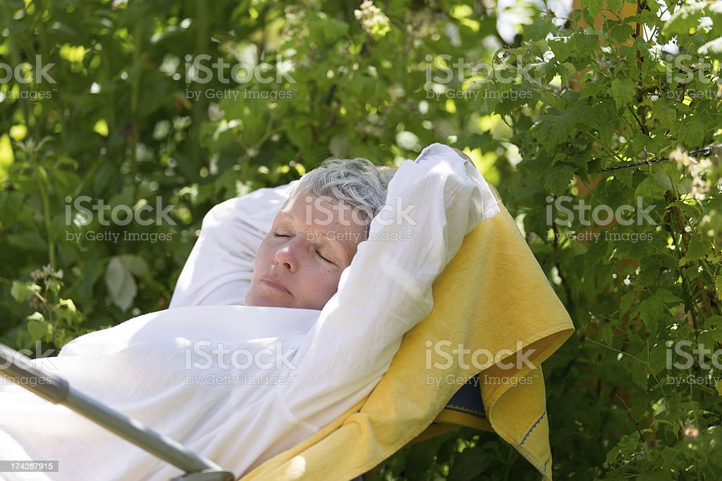Mature woman sleeping on lounger royalty-free stock photo