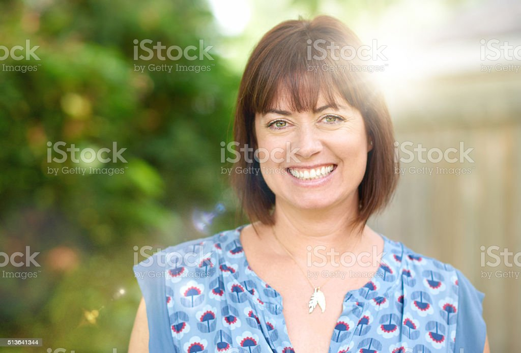 Mature woman smiling in nature stock photo
