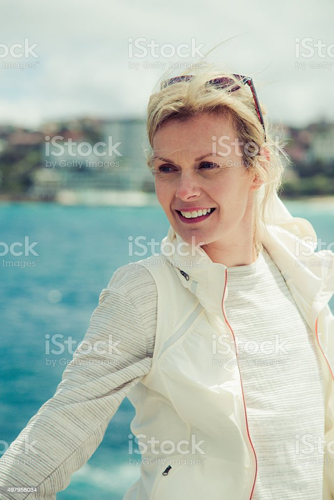 Mature woman smiling with coastline in background stock photo
