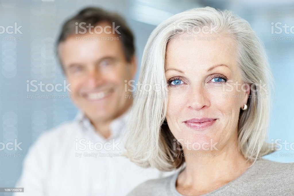Mature woman smiling with man in the background stock photo