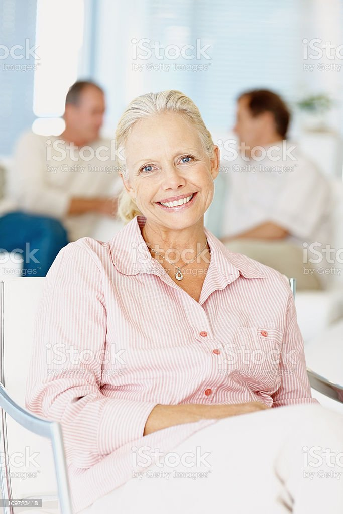 Mature woman smiling with people in the background royalty-free stock photo