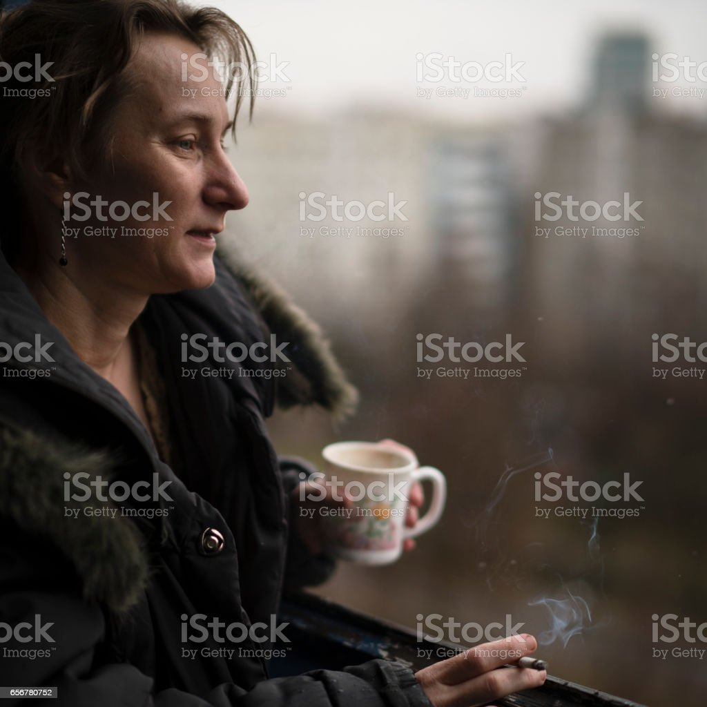 Mature woman smoking and drinking tea on the balcony stock photo