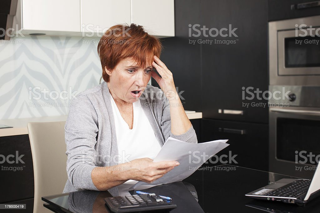 Mature woman sorting through her old receipts royalty-free stock photo