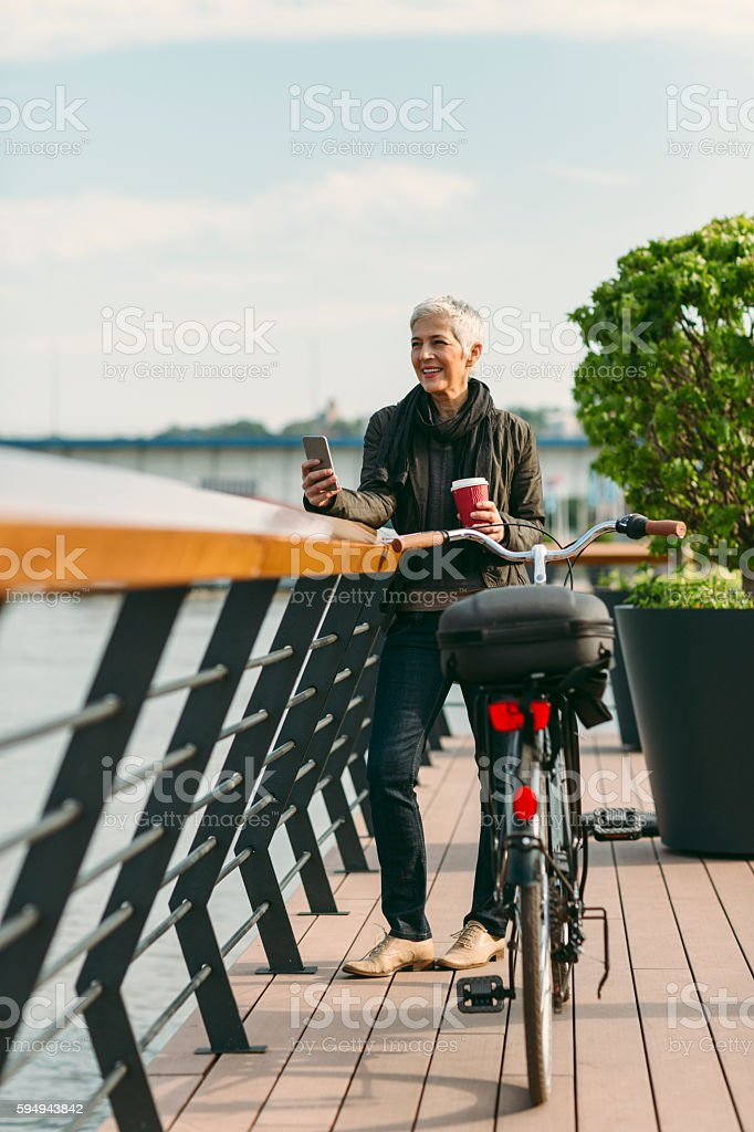 Mature Woman Standing On The Rivereside And Drinking Coffee. stock photo