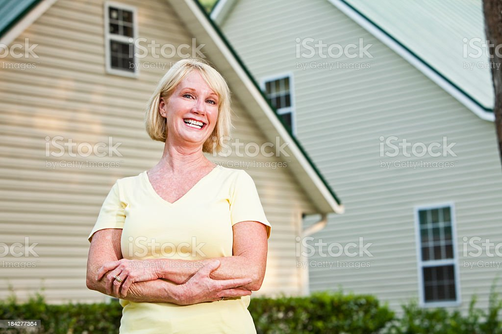 Mature woman standing outside home stock photo