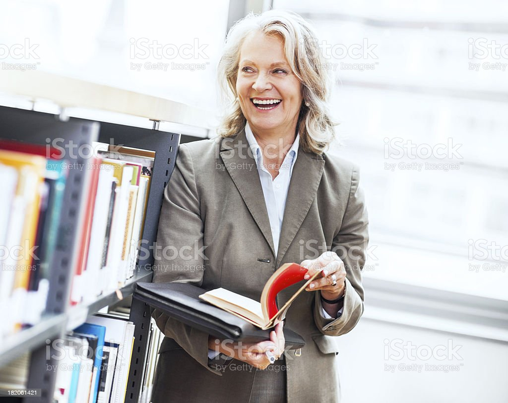 Mature woman standing with book in her hand. stock photo