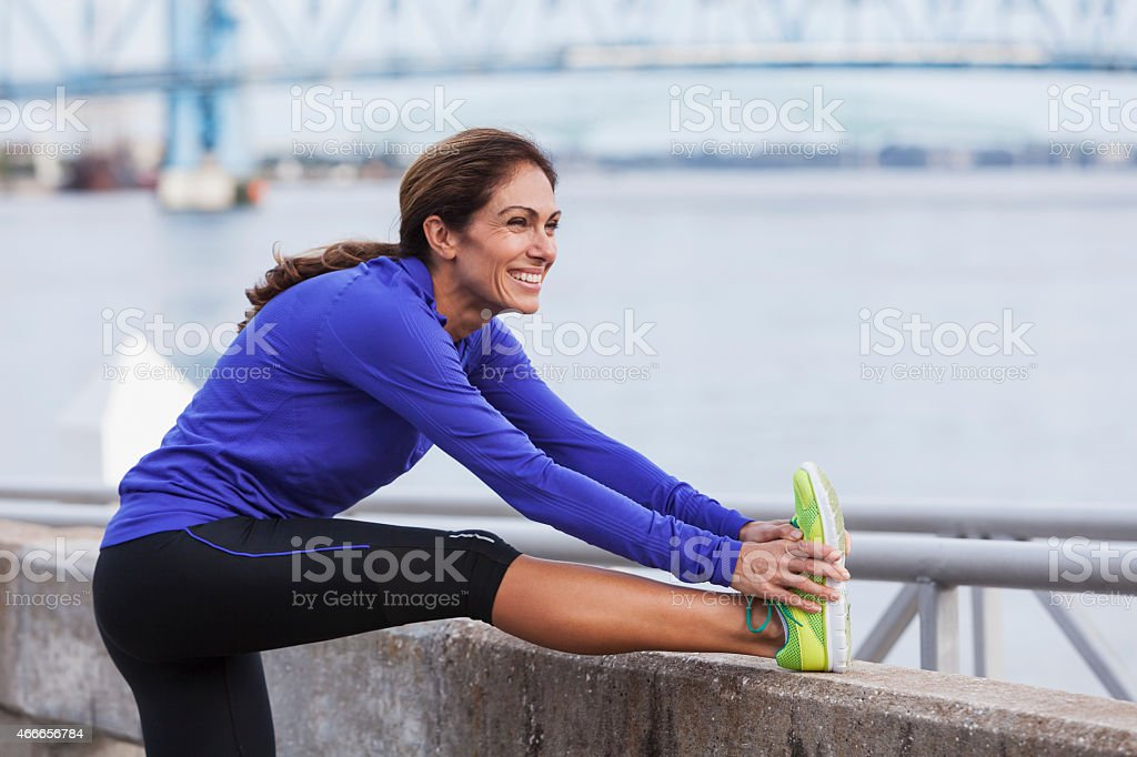 Mature woman stretching during a jog on waterfront stock photo