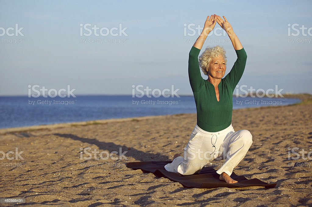 Mature woman stretching on the beach - Yoga stock photo