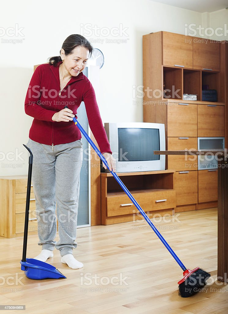 mature woman sweeping the floor stock photo