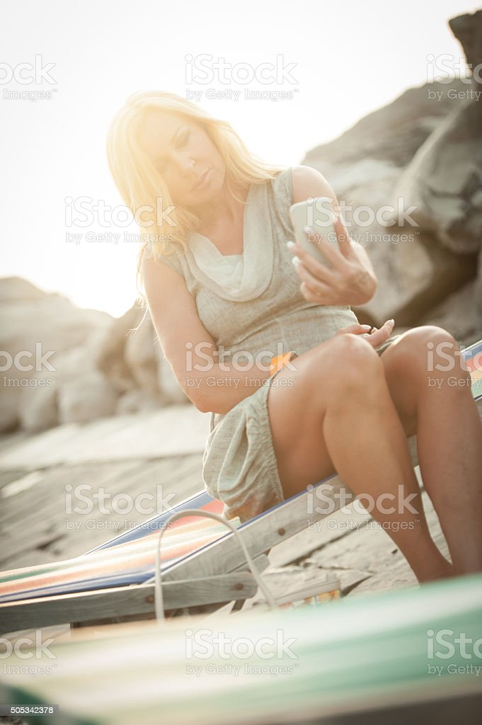 Mature woman taking mobile phone picture at sunset stock photo