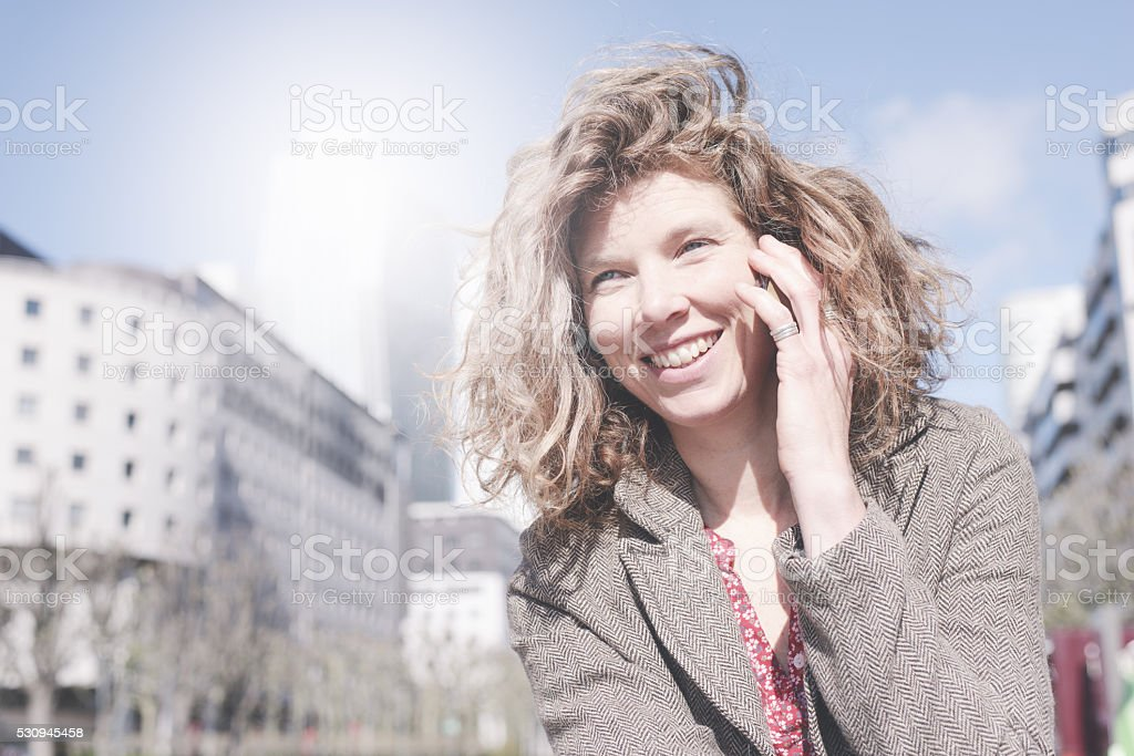 Mature Woman Talking on Smart Phone in Business District stock photo