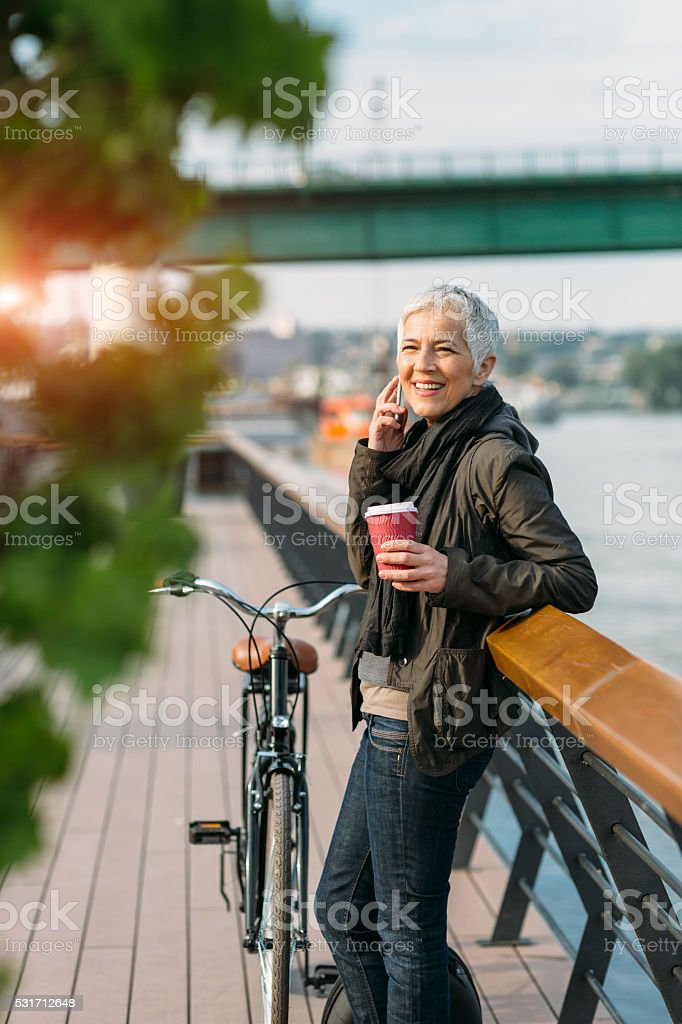Mature Woman Talking On The Phone And Drinking Coffee. stock photo