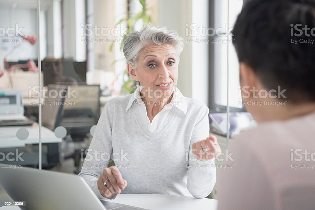 Mature woman talking to colleague in business meeting stock photo