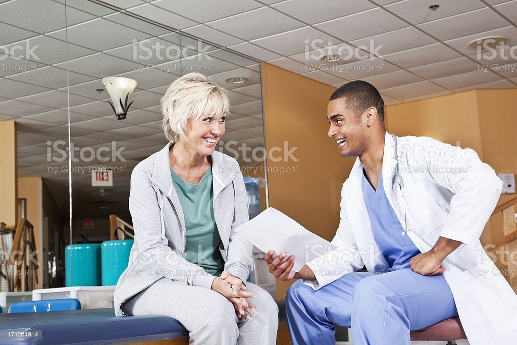 Mature woman talking to physical therapist stock photo
