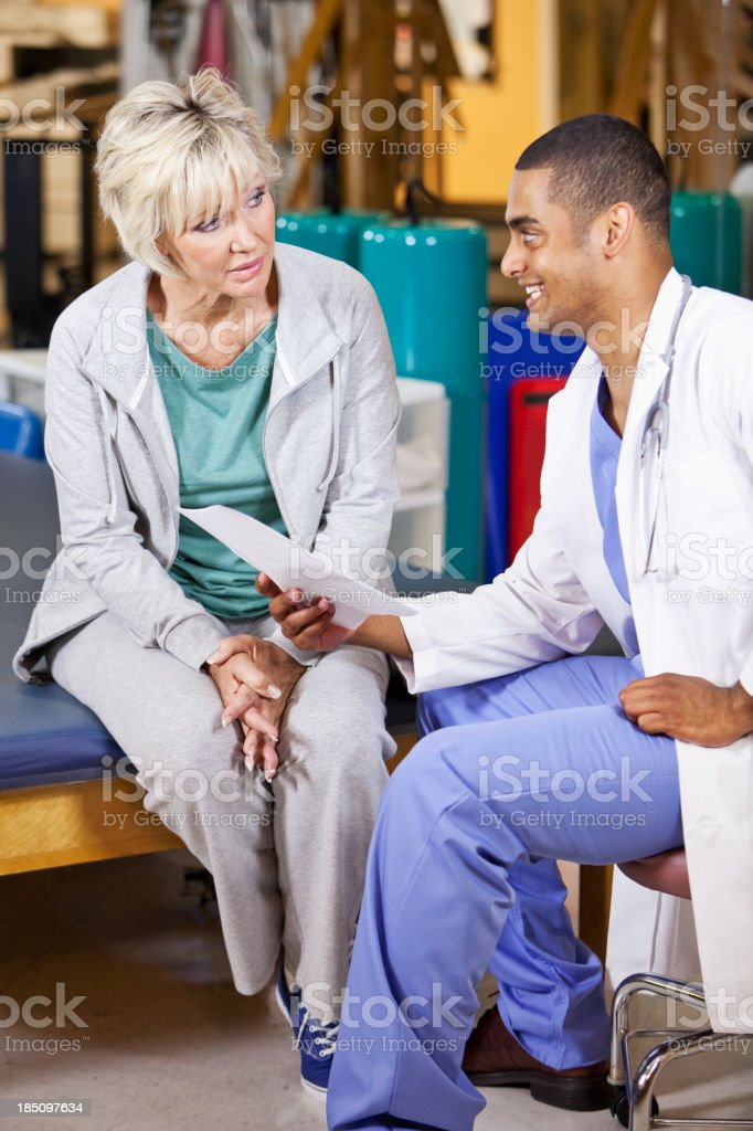 Mature woman talking with physical therapist stock photo