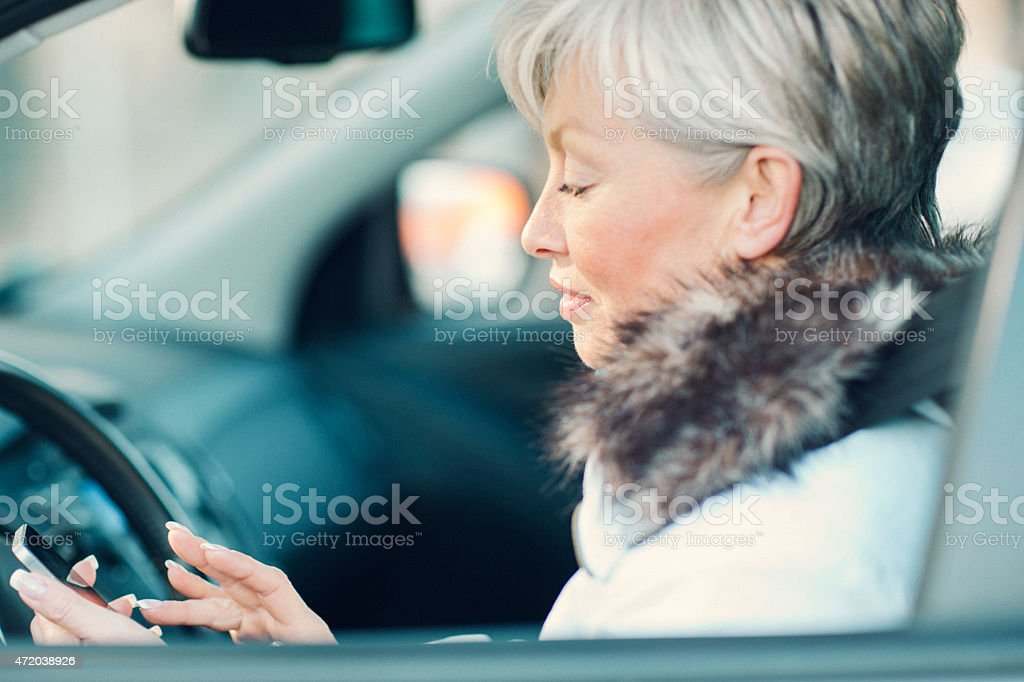 Mature Woman Texting in a car. stock photo