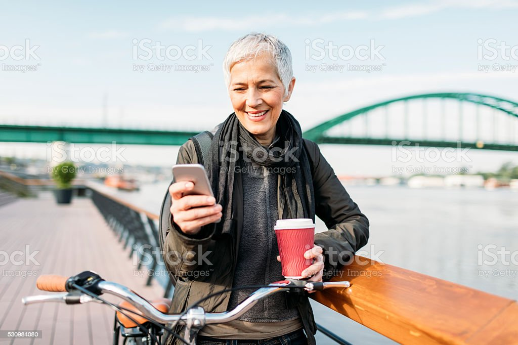 Mature Woman Texting On Her Smart Phone And Drinking Coffee stock photo