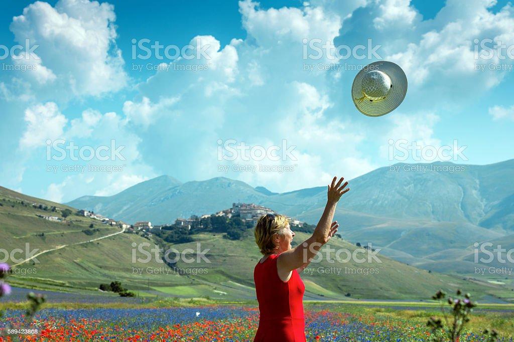 Mature Woman Throwing White Hat near Castelluccio, Italy stock photo