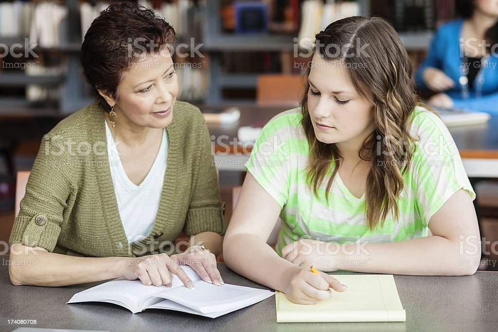 Mature Woman Tutors High School Student in Library royalty-free stock photo