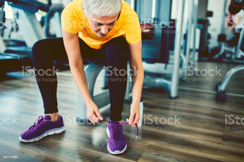 Mature Woman tying sports shoe stock photo